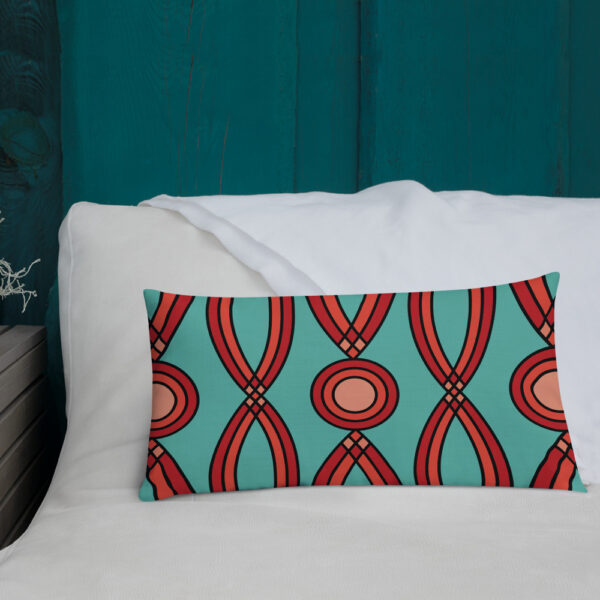 rectangle pillow with a red geometric pattern on a teal blue background sitting on a bed