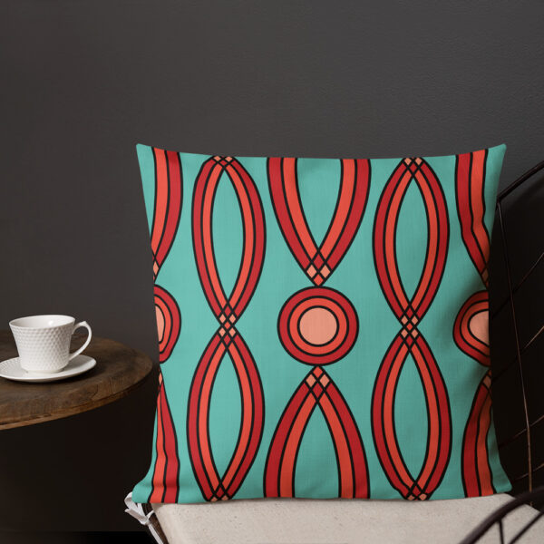 square pillow with a red geometric pattern on a teal blue background sitting on a chair next to a cup of coffee