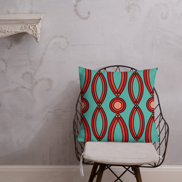 square pillow with a red geometric pattern on a teal blue background sitting on a chair