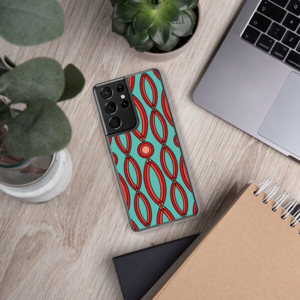 samsung phone case that has a red geometric shape pattern on a teal blue background sitting next to a laptop