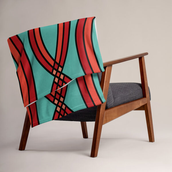 blanket with a red mosaic pattern on a teal blue background, draped over a chair
