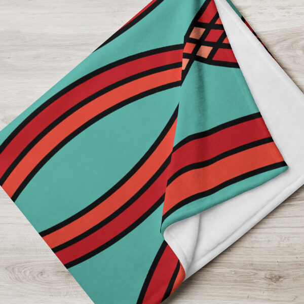 folded blanket with a red mosaic pattern on a teal blue background