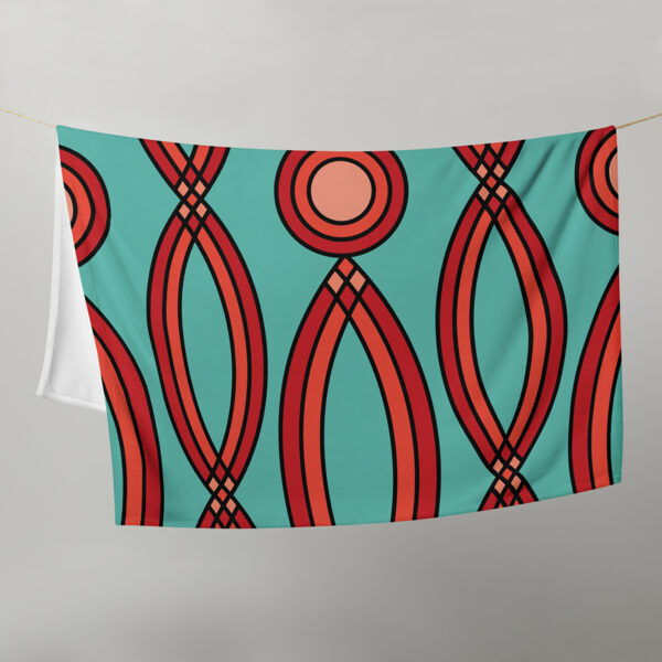blanket with a red mosaic pattern on a teal blue background, hanging on a clothes line