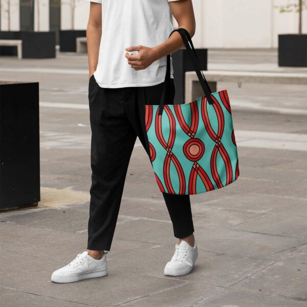 person holding a teal blue tote bag with a red geometric design and black handles