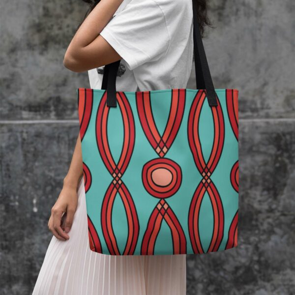 woman holding a teal blue tote bag with a red geometric design and black handles