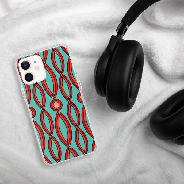 iphone case that has a red geometric shape pattern on a teal blue background sitting next to headphones