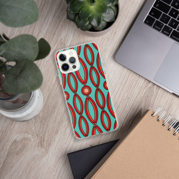 iphone case that has a red geometric shape pattern on a teal blue background sitting next to a laptop