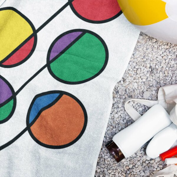 white beach towel with a colorful abstract design of six rainbow circles next to a water bottle