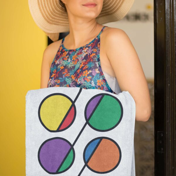 woman holding a white beach towel with a colorful abstract design of six rainbow circles