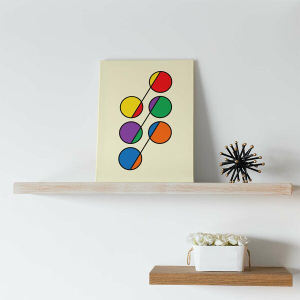 vertical stretched canvas print with six colorful circles in rainbow colors on a yellow background on a shelf