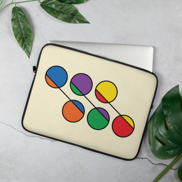 laptop sleeve with six circles in rainbow colors on a yellow background sitting on a table