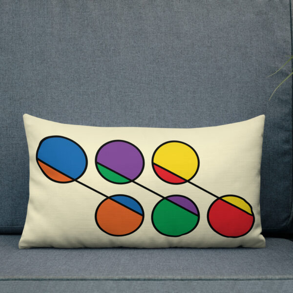 rectangle pillow with a design of six circles in rainbow colors on a yellow background sitting on a sofa
