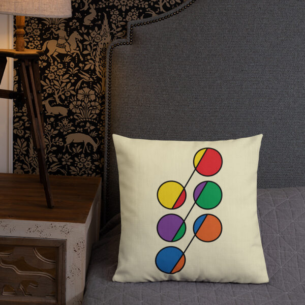 square pillow with a design of six circles in rainbow colors on a yellow background sitting on a bed