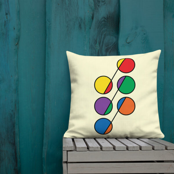 square pillow with a design of six circles in rainbow colors on a yellow background sitting on a bench