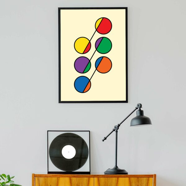 vertical fine art print with a colorful design of six circles in rainbow colors in a black frame hanging on a wall