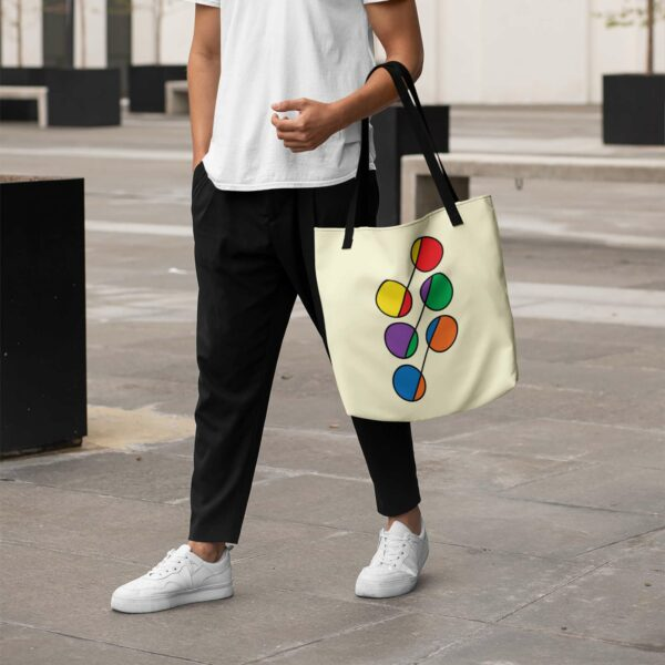 person holding a yellow tote bag with black handles and a design of six circles in rainbow colors
