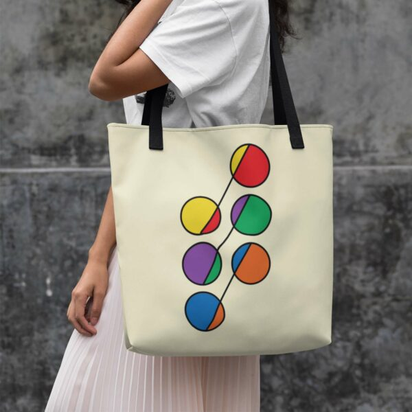 woman holding a yellow tote bag with black handles and a design of six circles in rainbow colors
