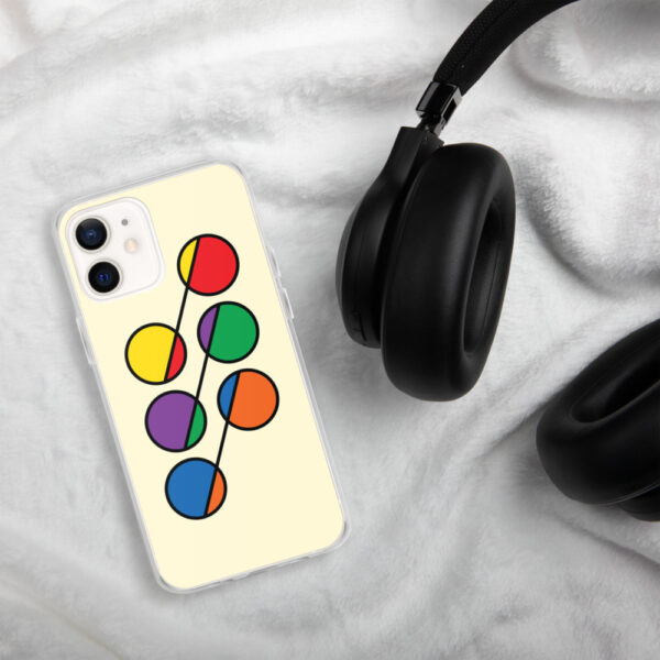iphone case that has six colorful circles in rainbow colors on a yellow background sitting next to headphones