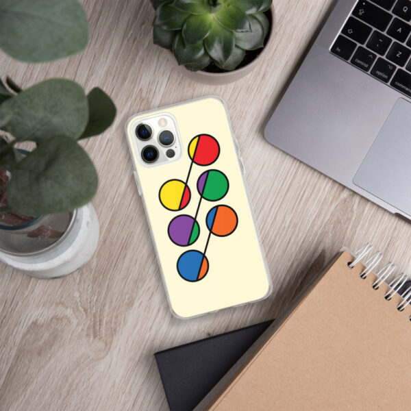 iphone case that has six colorful circles in rainbow colors on a yellow background sitting next to a laptop