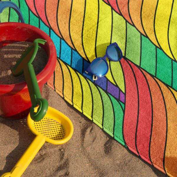 beach towel with a colorful abstract rainbow design on sand with sunglasses
