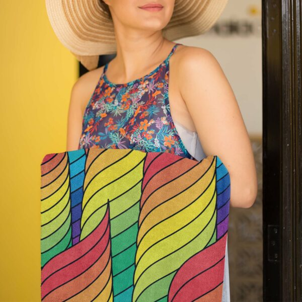 woman holding a beach towel with a colorful abstract rainbow design