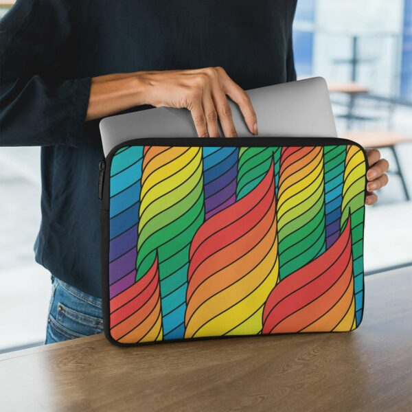 person holding a laptop sleeve with an abstract design of spirals in rainbow colors