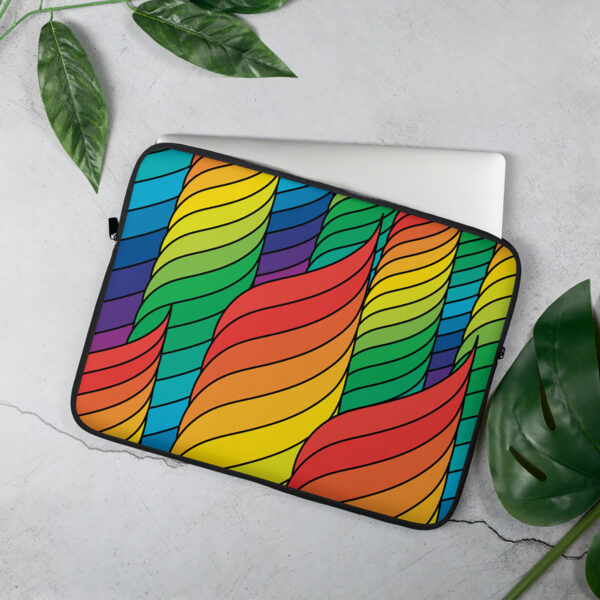 laptop sleeve with an abstract design of spirals in rainbow colors sitting on a table