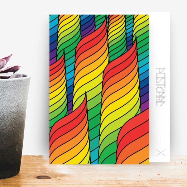 postcard with an abstract rainbow spiral design sitting on a table