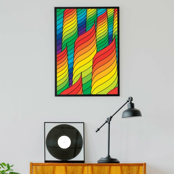 vertical fine art print with an abstract design of rainbow spirals in a black frame hanging on a wall