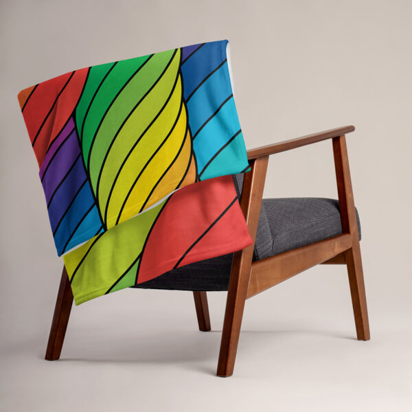 blanket with an abstract design of spirals in rainbow colors, draped over a chair