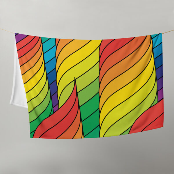 blanket with an abstract design of spirals in rainbow colors, hanging on a clothes line
