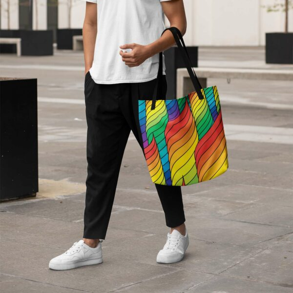 person holding a tote bag with black handles and an abstract rainbow spiral design