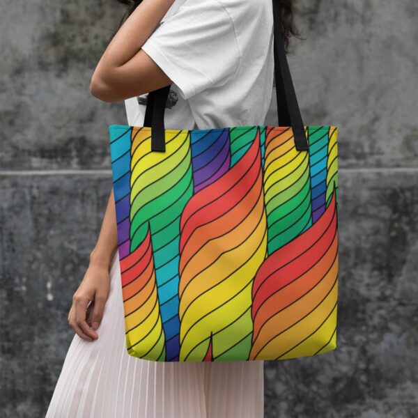 woman holding a tote bag with black handles and an abstract rainbow spiral design