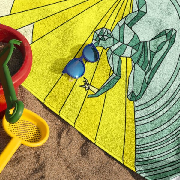 beach towel with a yellow and green spirit of detroit design on sand with sunglasses