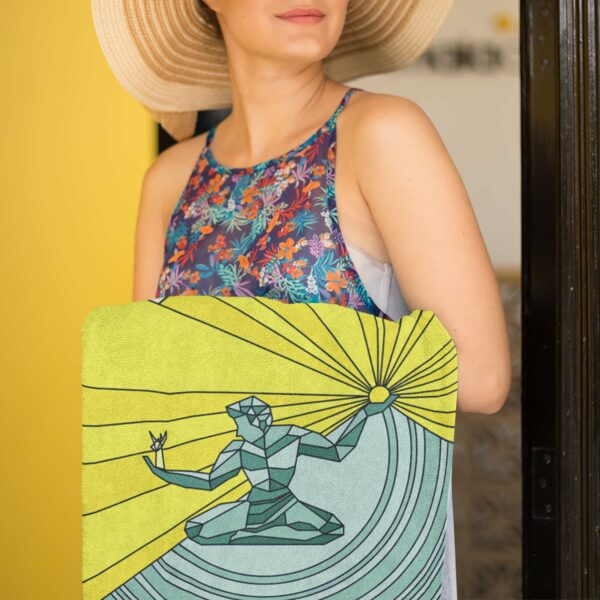 woman holding a beach towel with a yellow and green spirit of detroit design