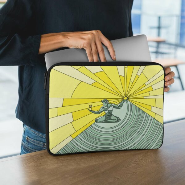 person holding a laptop sleeve with a yellow and green illustration of the spirit of detroit