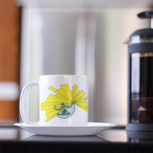 white ceramic coffee mug with a yellow and green illustration of the spirit of detroit on the side sitting on a saucer