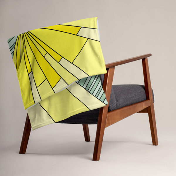 blanket with a yellow and green spirit of detroit design, draped over a chair