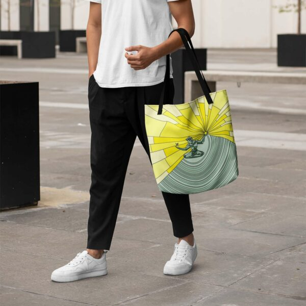 person holding a tote bag with black handles and a yellow and green spirit of detroit design