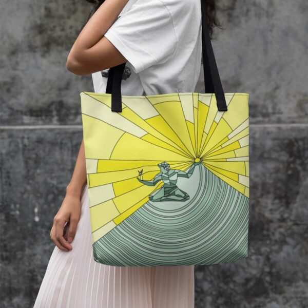 woman holding a tote bag with black handles and a yellow and green spirit of detroit design