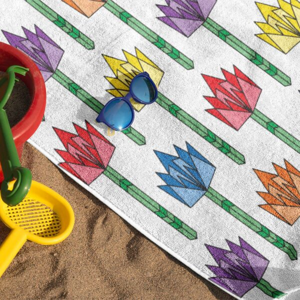 white beach towel with a pattern of colorful tulips in rainbow colors on sand with sunglasses
