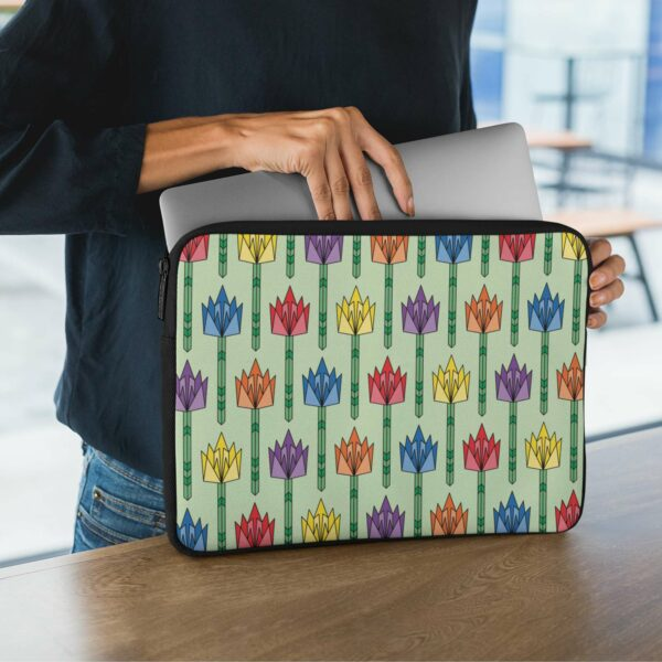 person holding a laptop sleeve with a pattern of tulip flowers in a mid-century design with rainbow colors