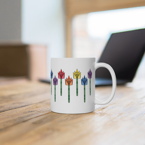 11 ounce white ceramic coffee mug with tulip flowers in rainbow colors around the sides sitting on a table