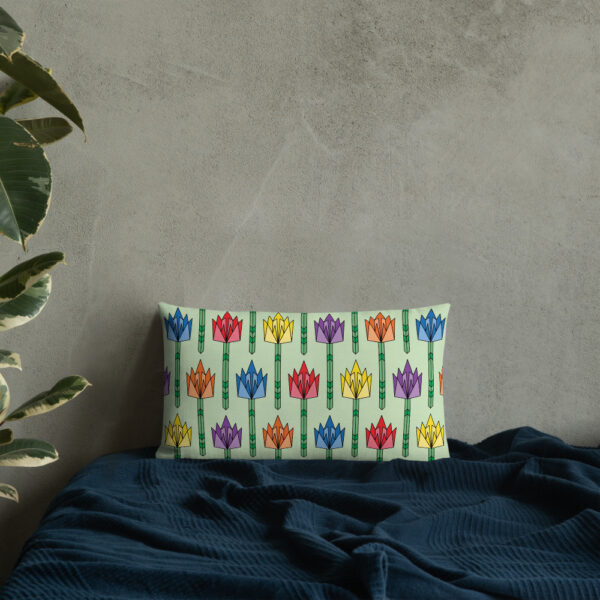 rectangle pillow with a pattern of tulip flowers in rainbow colors and a mid-century style sitting on a bed