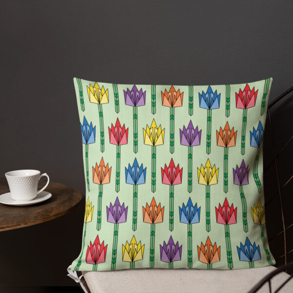 square pillow with a pattern of tulip flowers in rainbow colors and a mid-century style sitting on a chair next to a cup of coffee