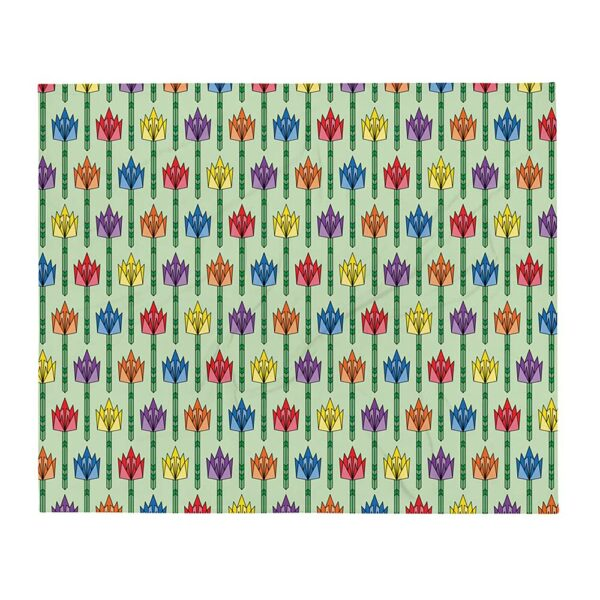 blanket with a pattern of geometric tulips in rainbow colors on a light green background