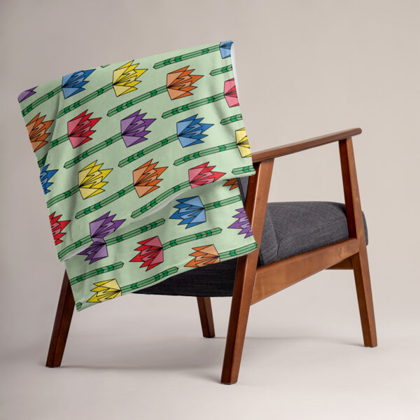 blanket with a pattern of geometric tulips in rainbow colors on a light green background, draped over a chair