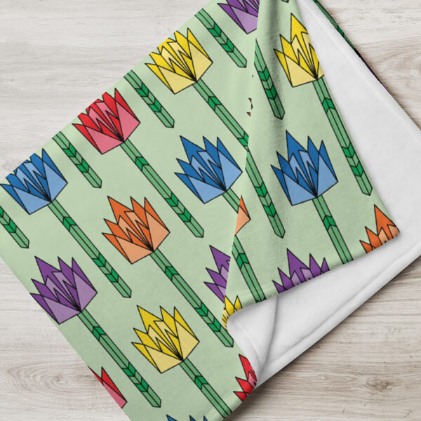 folded blanket with a pattern of geometric tulips in rainbow colors on a light green background