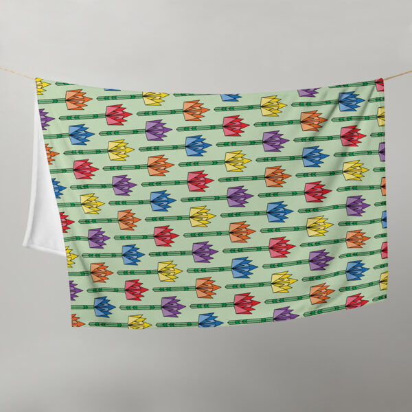 blanket with a pattern of geometric tulips in rainbow colors on a light green background, hanging on a clothes line