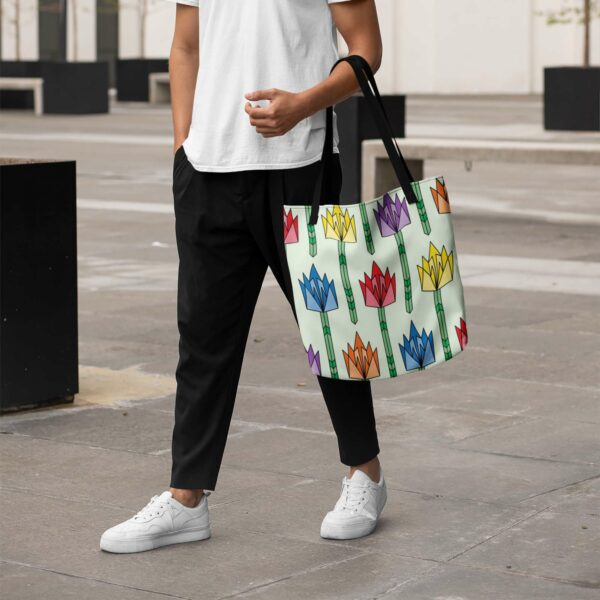 person holding a light green tote bag with black handles and a pattern of tulip flowers in rainbow colors